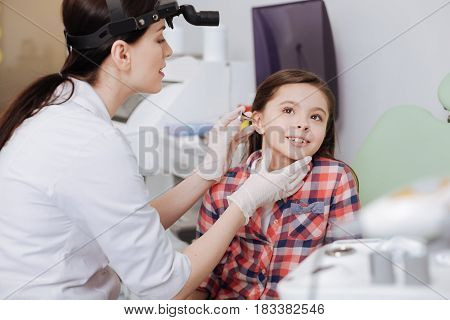 Do not be afraid. Positive delighted girl wearing checked shirt showing her teeth looking upwards