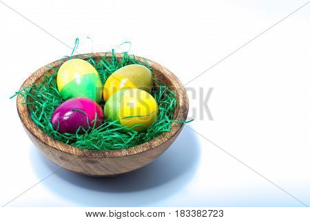 Four Hand Painted Easter Eggs On A Wood Bowl Isolated On White Background
