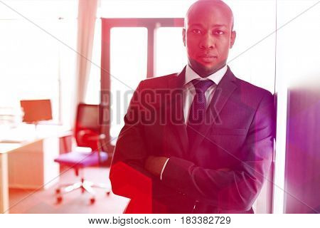 Portrait of young businessman standing arms crossed leaning on cupboard in office