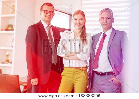 Portrait of confident young businesswoman with male colleagues in office
