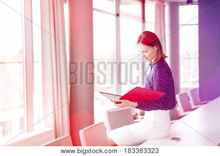 Young businesswoman reading file while sitting on conference table in office