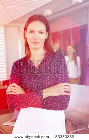 Portrait of young businesswoman standing arms crossed with colleagues in background at office