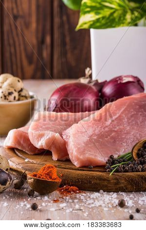 Few Slices Of Raw Pork Meat On Vintage Wooden Plate