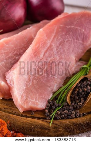 Few Slices Of Raw Pork Meat On Wooden Plate With Pepper