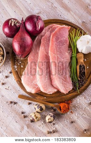 Few Slices Of Raw Pork Meat On Wooden Plate With Spices