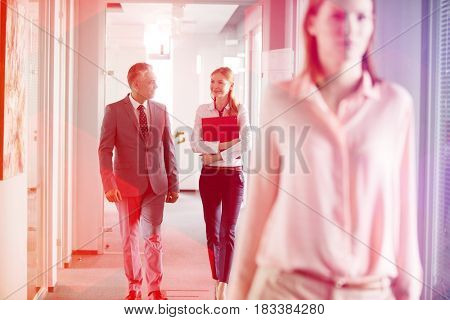 Businessman and businesswoman talking while walking in office corridor with female colleague in foreground
