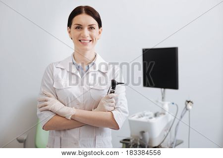 You are welcome. Beautiful doctor wearing white smock and rubber gloves holding otoscope in right hand while crossing arms on chest