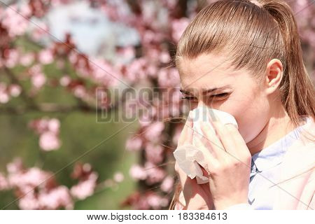 Sneezing young girl with nose wiper among blooming trees in park