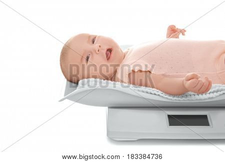 Cute little baby lying on scales against white background