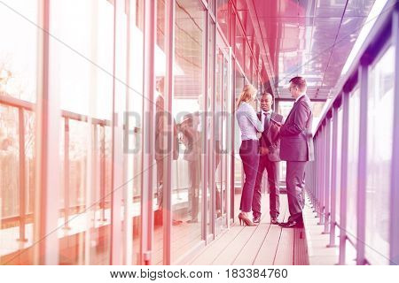 Full length of multi-ethnic business people discussing on office balcony