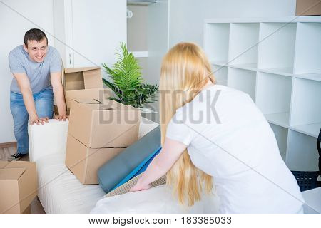 Young couple carrying sofa in their new house