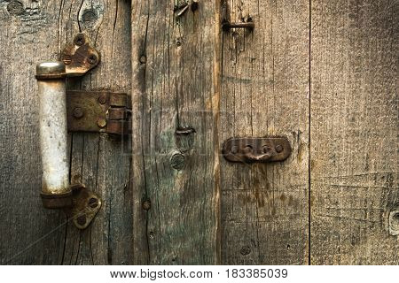 Photo of an old door made of wood and a metal retro handle