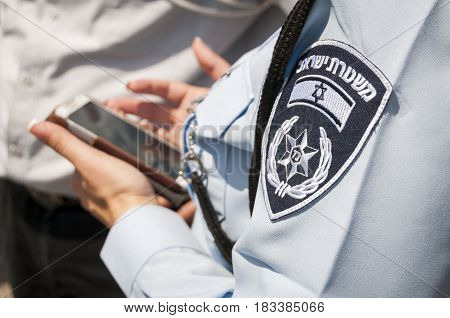 Unknown Israeli female police officer with a Police of Israel official emblem on her uniform holding cellular phone in her hands as if questioning a suspect. Tel Aviv, Israel, April 2014.