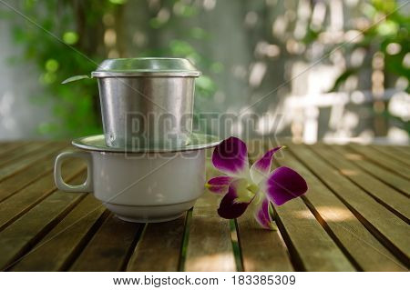 Violet dendrobium orchid flower beside cup of black coffee with filter above on wooden table with bright background