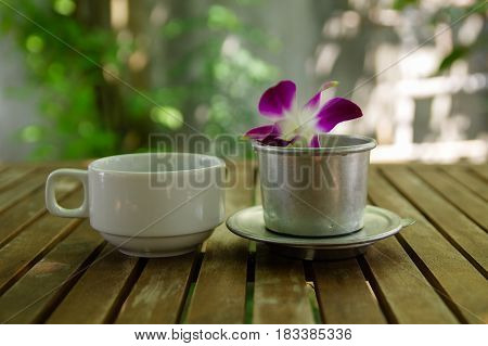 Violet dendrobium orchid flower & cup of black coffee with coffee filter on wooden table with bright background