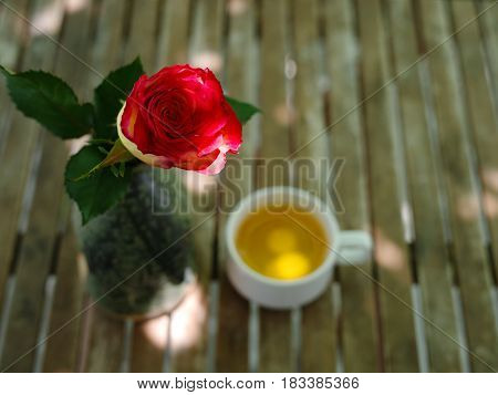 Red rose with blurry cup of jasmine tea in the background on a wooden table in garden