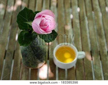 Pink rose with blurry cup of jasmine tea in the background on a wooden table in garden