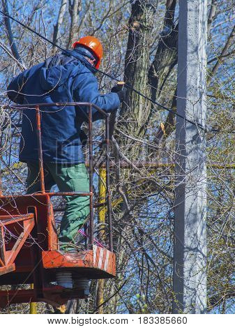 The worker on machine lift at an electric pole