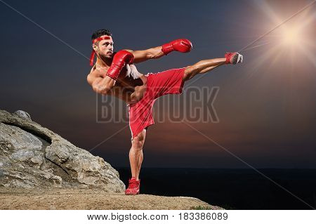 Young shirtless boxer with muscular strong body training outdoors kickboxing boxing martial arts defense protection confidence dedication motivation sport fitness fit lifestyle workout exercising