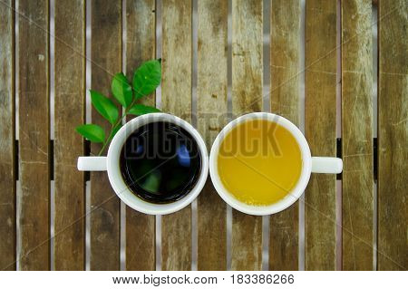 Cup of black coffee cup of jasmine tea with a green leaf on wooden table. Top view.