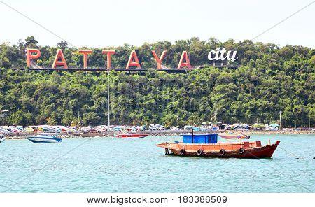 Pattaya, Thailand - December 05, 2009: Boats and Pattaya City sign on shore