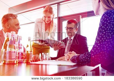 Young businesswoman showing project to businessman during meeting in office