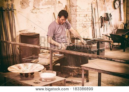 Murano island Italy - April 23 2017: Glassblowing artisan at work in a crystal glass workshop in Murano island Venice. Murano glassmakers use the same tools as their ancestors have thousands of years ago.