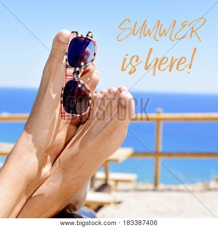 closeup of a young caucasian man who is relaxing near the ocean, with a pair of sunglasses hanging of his bare feet and the text summer is here