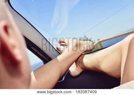 closeup of a young caucasian man relaxing in the passenger seat of a car, with his bare feet on the dashboard, near the ocean