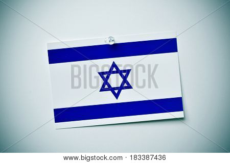 closeup of a flag of israel pinned with a push-pin to an off-white background with a vignette effect