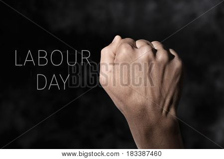 closeup of the raised fist of a young man against a gradient dark gray background and the text labour day