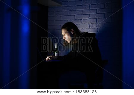 Photo of young concentrated man using laptop computer at home indoors at night. Looking aside.