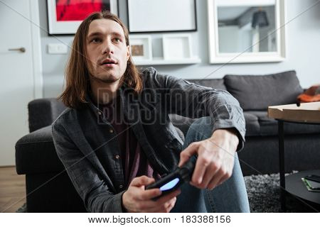 Photo of young concentrated man sitting at home indoors play games with joystick. Looking aside.