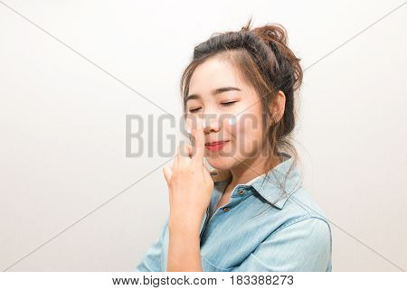 Young Asian Woman Applying Moisturizing Cream On Her Face