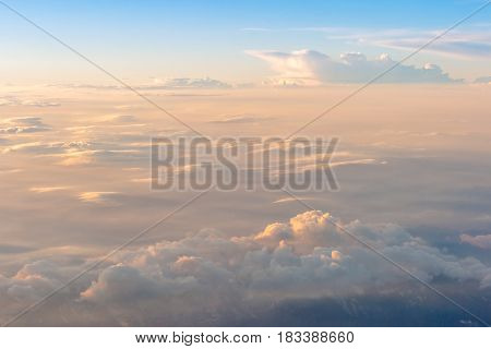 The colorful soft sky above the clouds and some mountains silhouettes below - airplane traveling in the summer