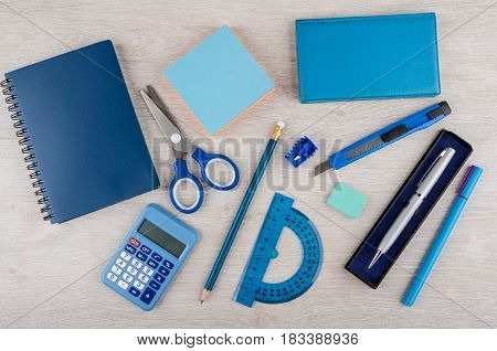 Different Stationery Tools Of Blue Color On Light Wooden Table