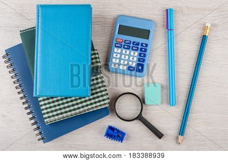 Heap Of Notepads, Calculator And Other Stationery Tools On Table