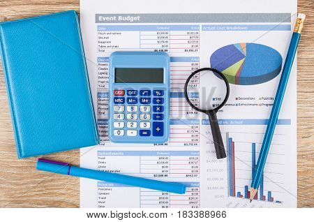 Printout Of Event Budget, Calculator, Notepad, Magnifying Glass And Pen