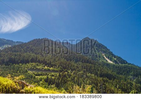 Motion picture - Travelling by bus in Italian Alps - Alpine landscapes with motion-blurred foreground Highly in mountains at hot shiny summer day with blue cloudy sky.