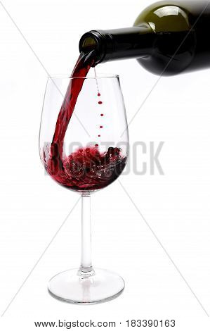 Pour an excellent red vintage wine in an elegant crystal goblet isolated on white background.