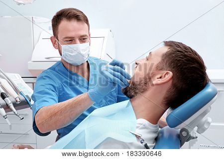 Dentist examining patient's teeth in clinic