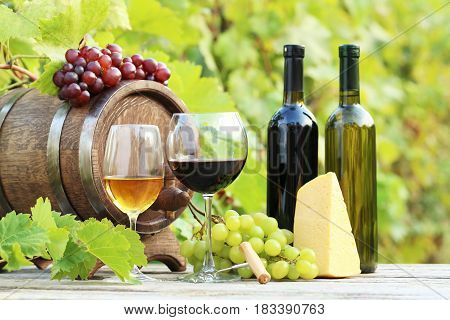 Wine In Glasses With Bunch Of Grape And Cheese On Wooden Table
