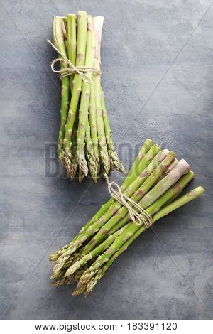 Heap Of Green Asparagus On Grey Wooden Table