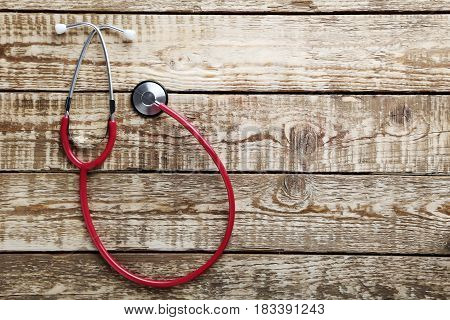 Stethoscope on a grey wooden table, close up