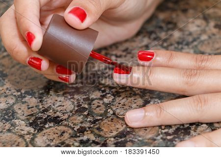 The girl nail painting red color by herself