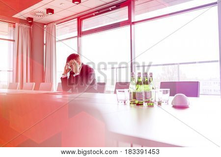 Mature businessman suffering from headache at conference table