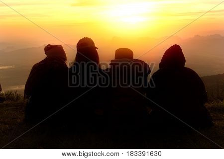 Silhouette of friends sitting down and looking at the sunrise together