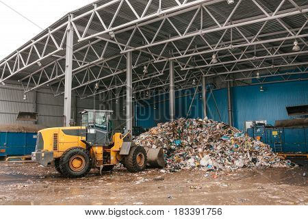 The bulldozer will clean the waste dump. Waste processing plant. Technological process. Business for sorting and processing of waste.