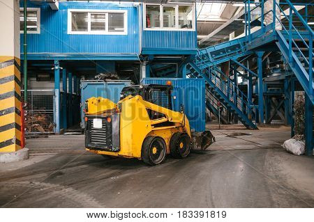 An industrial machine is driving through the plant. Waste processing plant. Recycling and storage of waste for further disposal. Business for sorting and processing of waste.