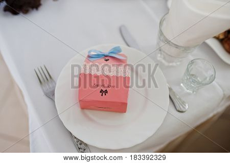 Small Box With Candies At Dish On Wedding Table Of Guests With Sign Sweet Love.